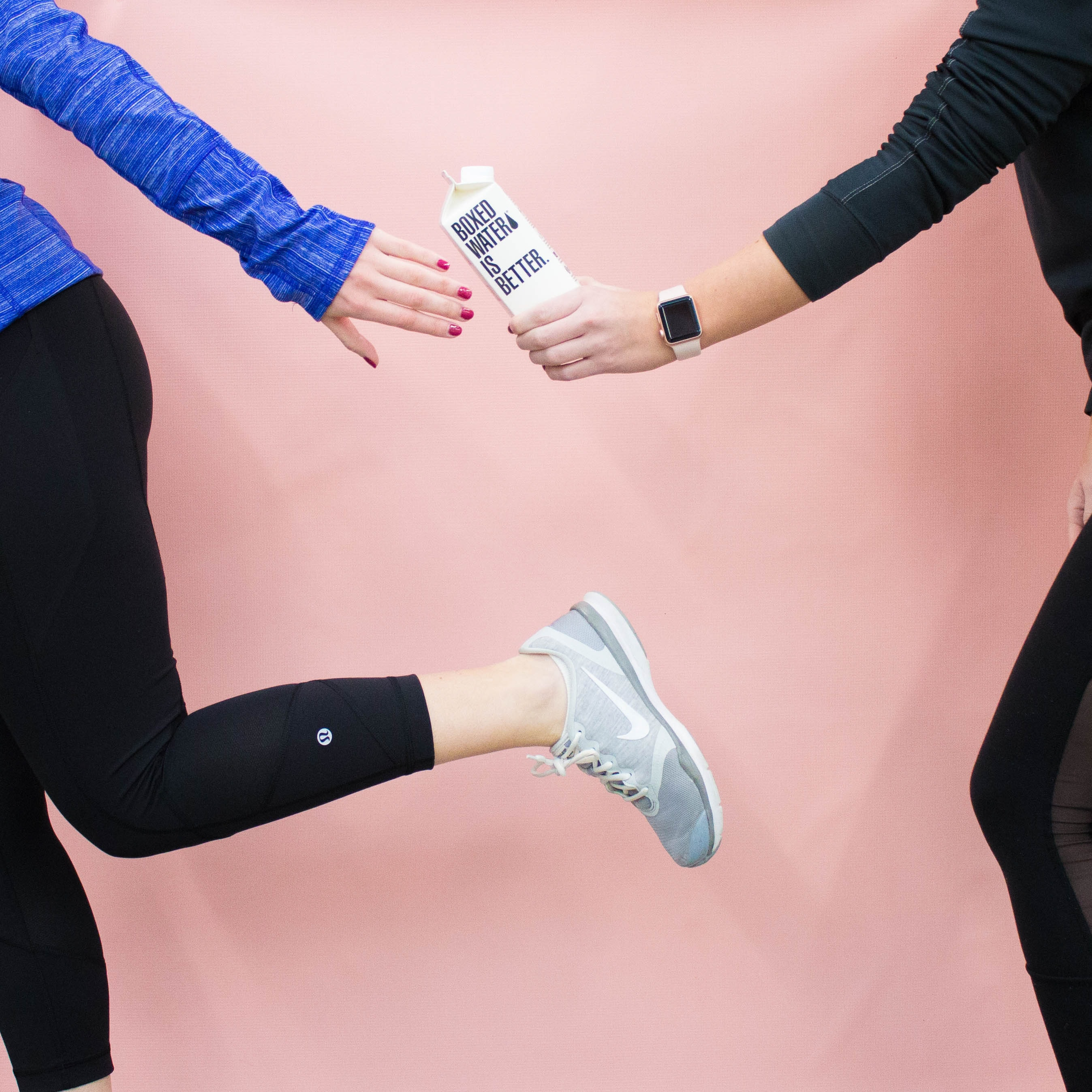 Two people running pass a Boxed Water carton
