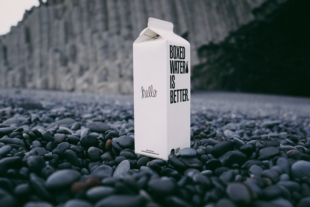 A carton of Boxed Water on a black beach