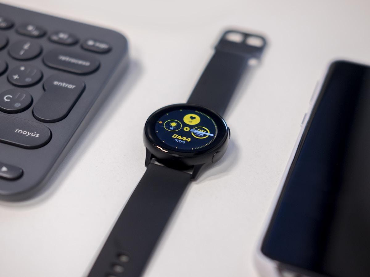 round black watch beside gray keyboard