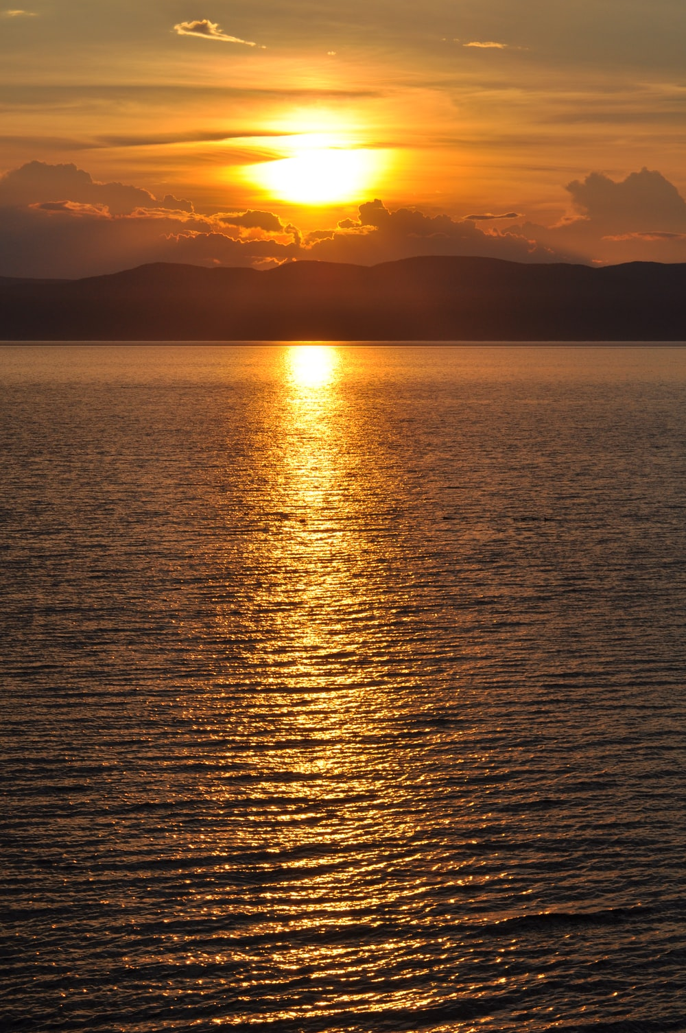 calm body of water overlooking mountain range during golden hour
