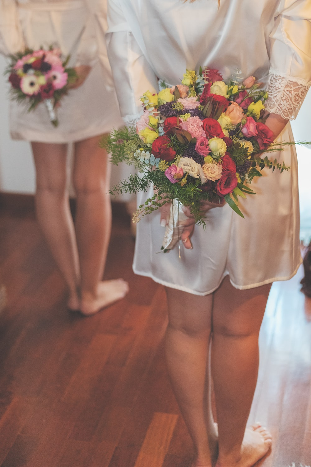 two person wearing white silk robes while holding multicolored bouquets