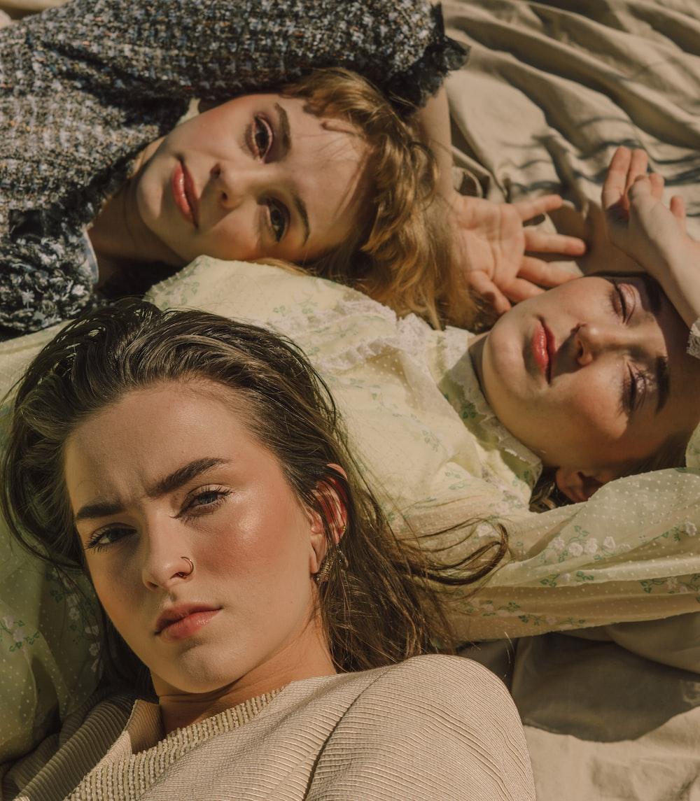 three women lying on white surface