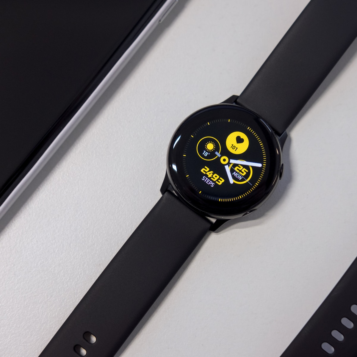 turned-on black smartwatch on white surface