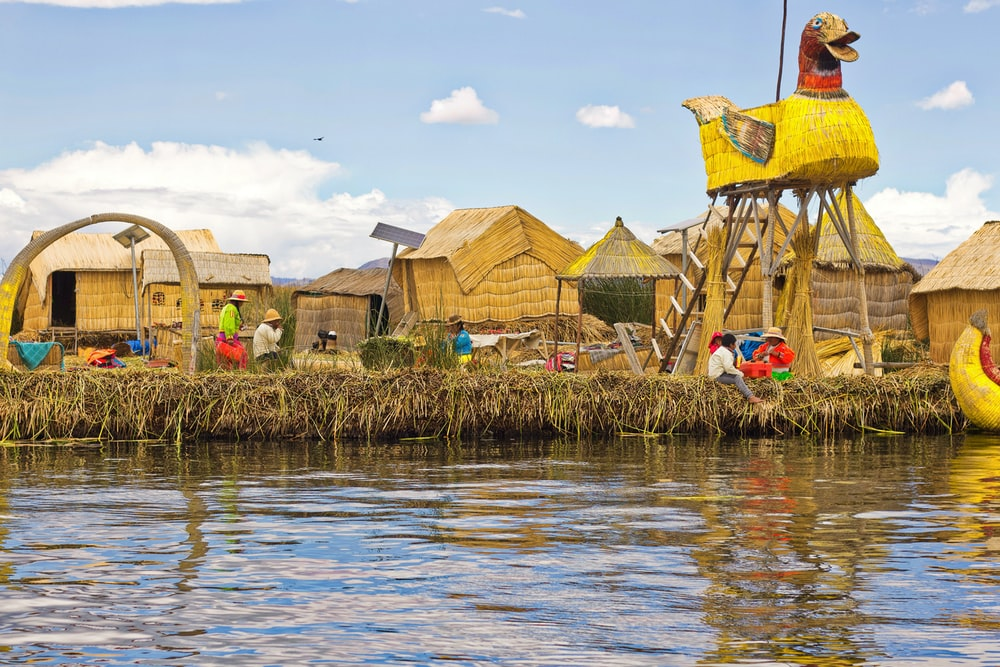 people near brown thatched houses across river