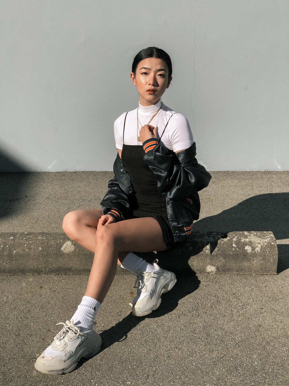 woman sitting on gray concrete surface