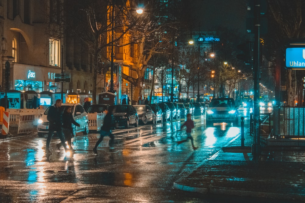 people crossing on street during nighttime