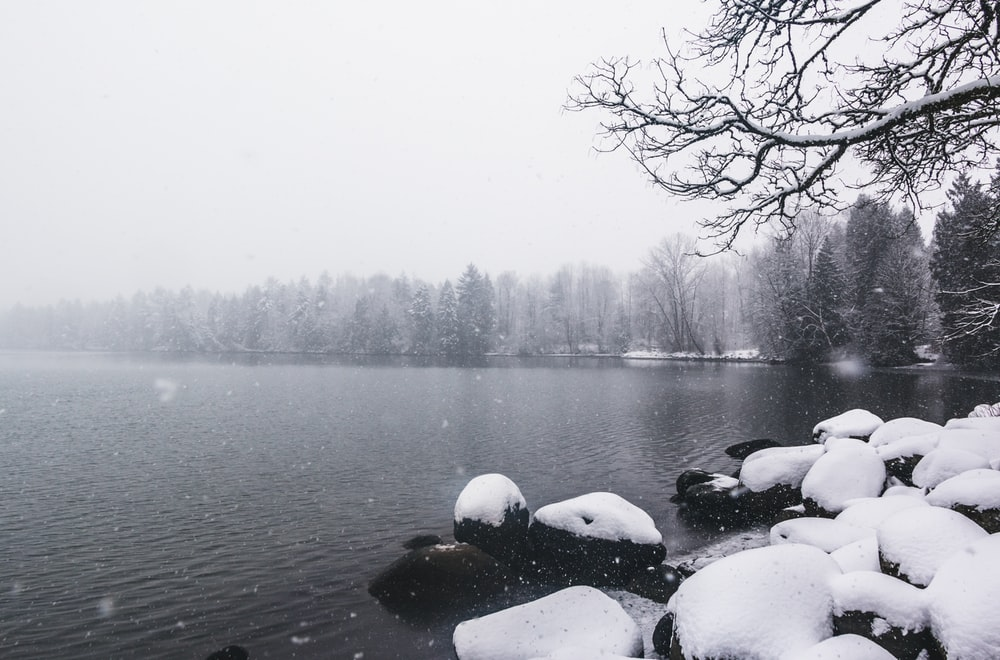 rocks covered with snow near body of water