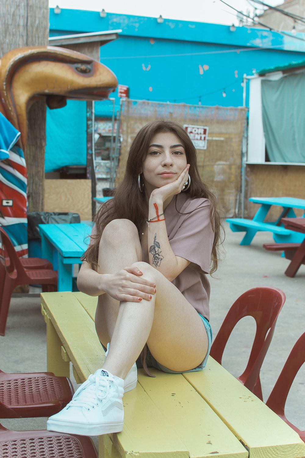 woman wearing beige screw-neck shirt and blue short sitting on yellow wooden bench
