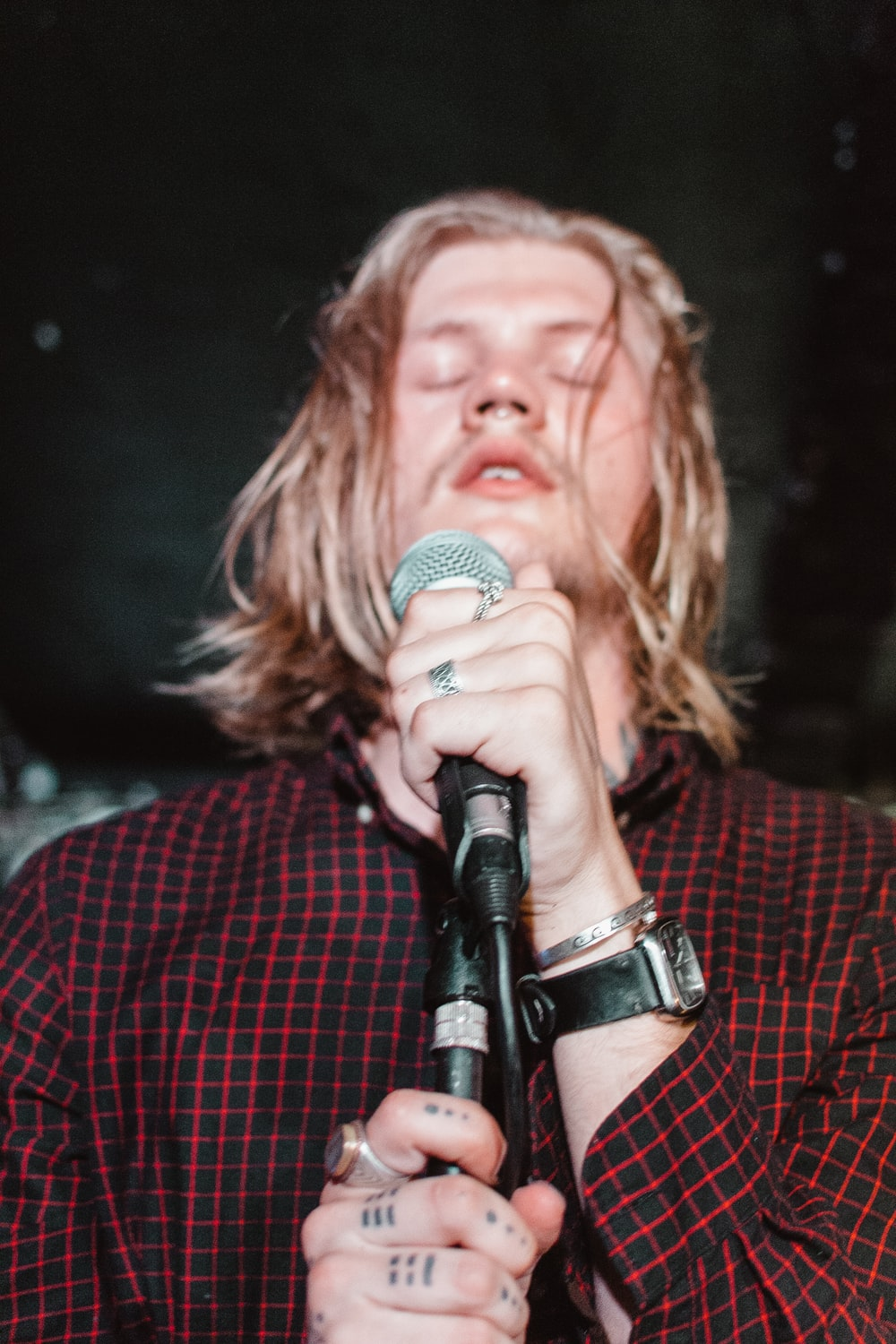 man holding black microphone with eyes close