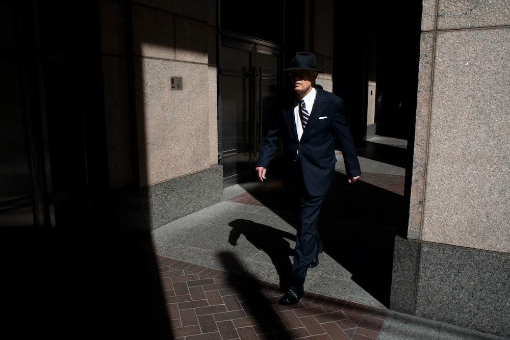 man wearing suit walking on pathway during daytime