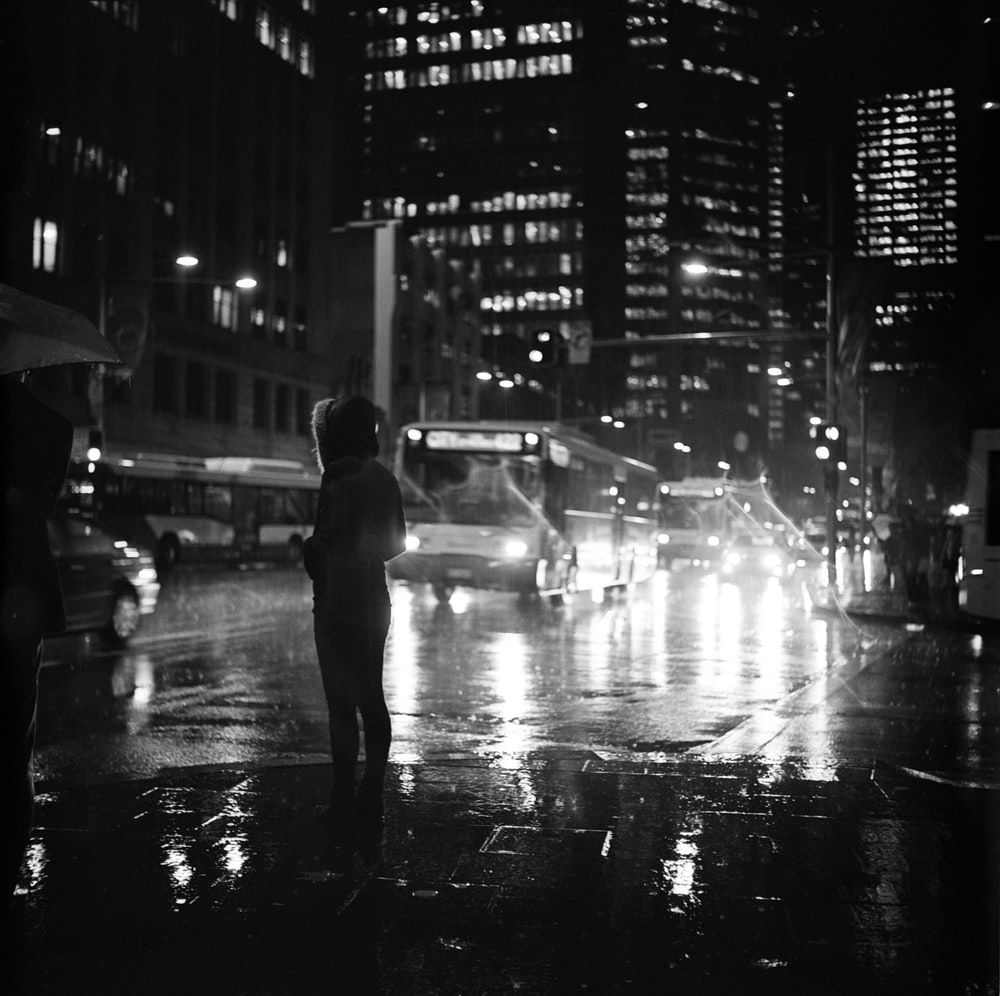 person standing on road in grayscale photography