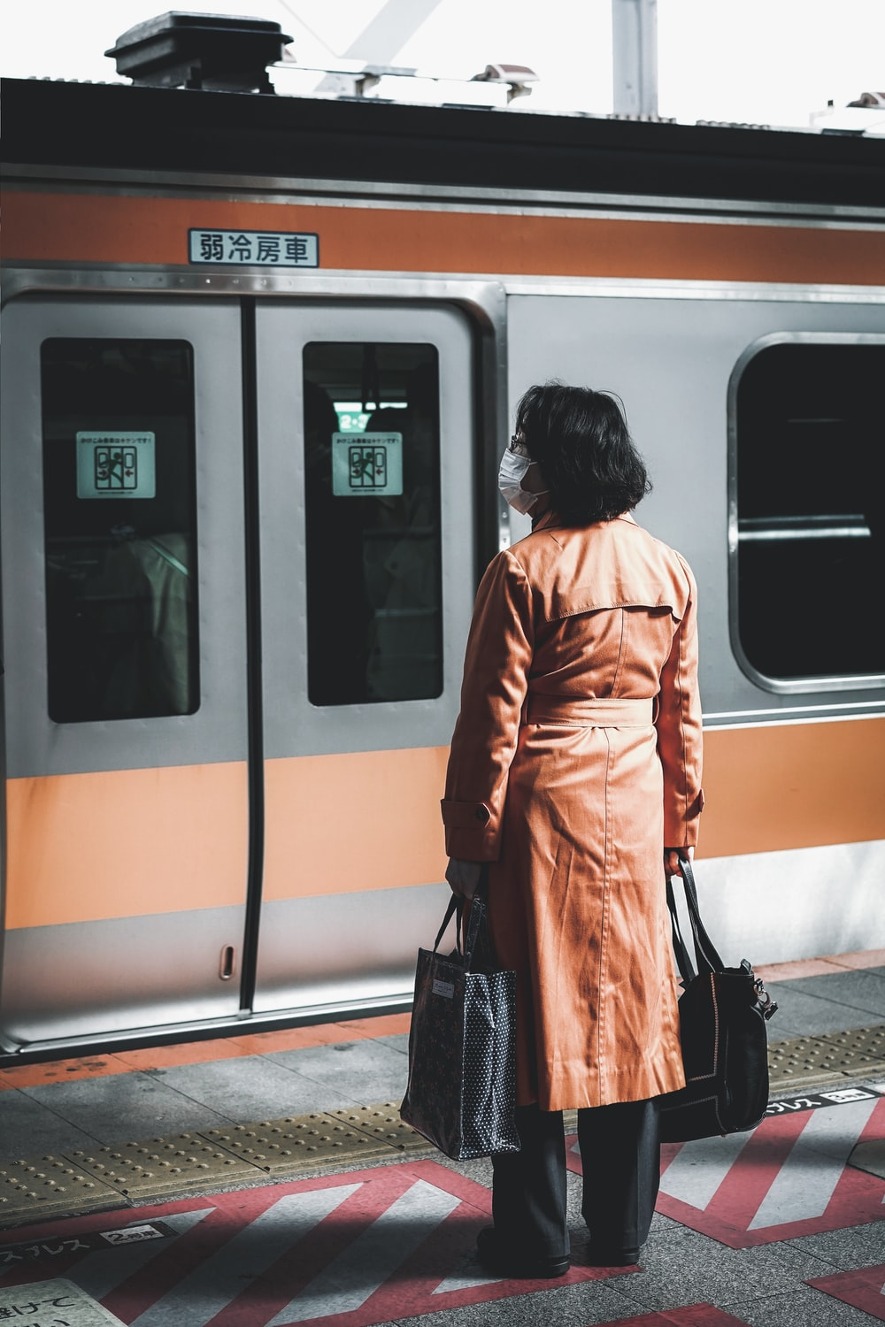 woman wearing brown coat standing in-front of grey train