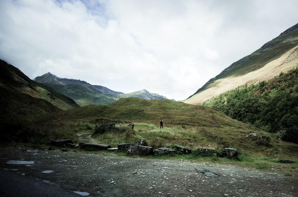 person walking on grass field surrounding mountain scenery