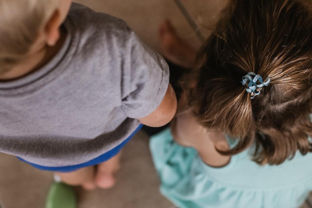 boy wearing t-shirt standing beside girl wearing teal dress