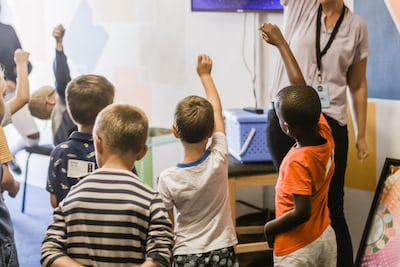 teacher teaching children raising hands in classroom