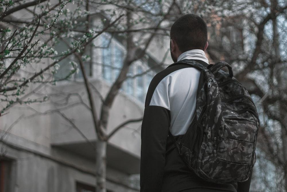 man standing under tree during daytime