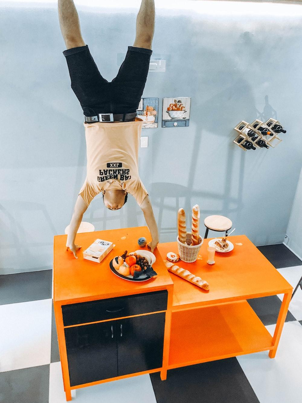 man standing upside down in orange and black cabinet