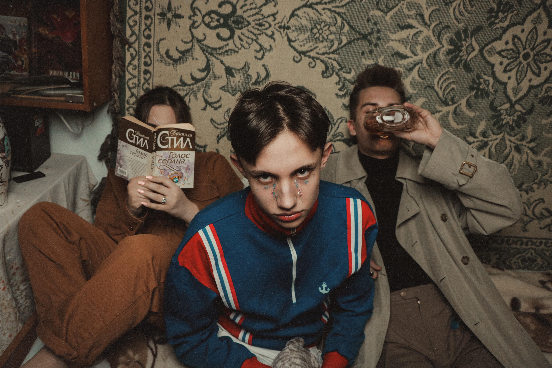 3 man sitting on beige bed