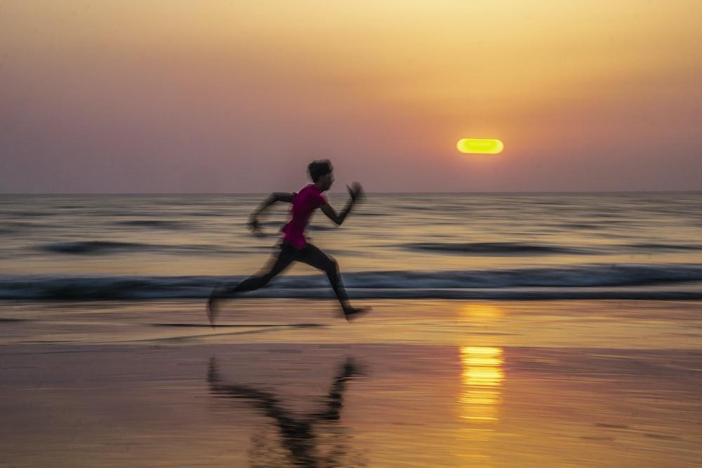 man running along seashore during golden hour