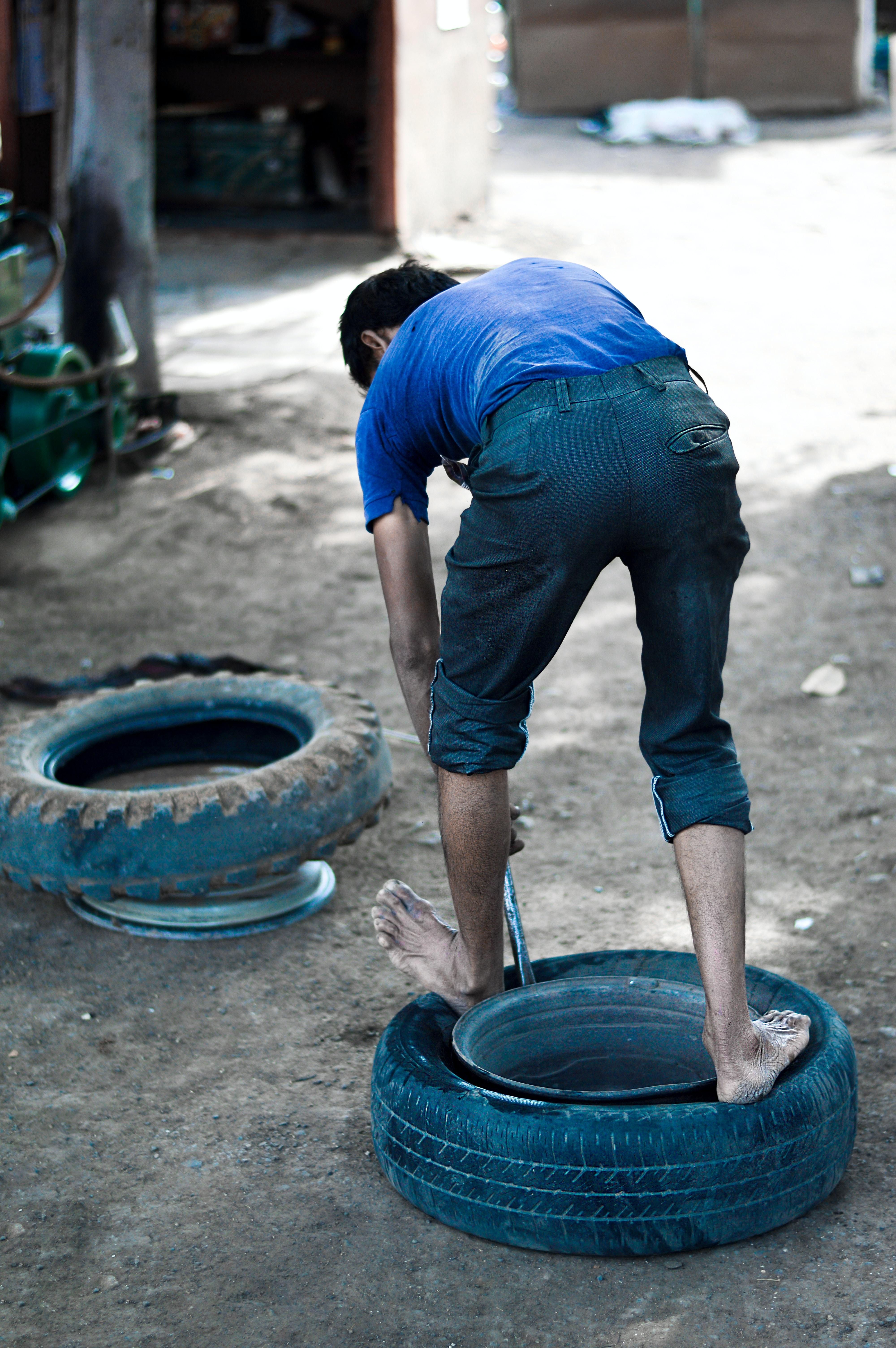 man changing tire during daytime