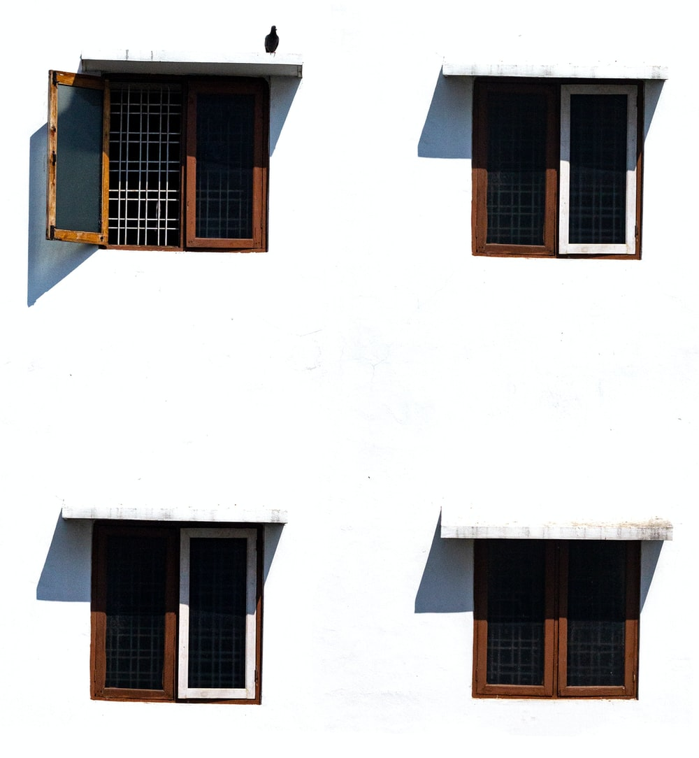 minimalist photography of white wall with four brown wooden windows