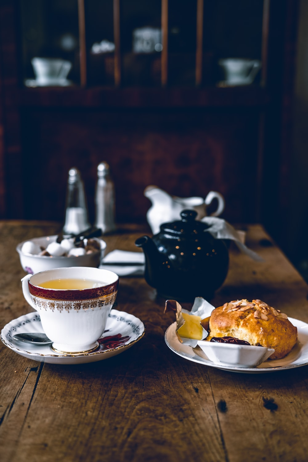 coffee pot beside bread on plate and teapot on table