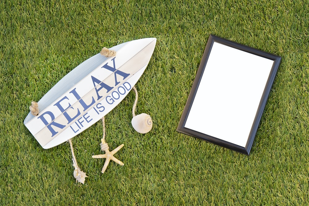 black photo framed and relax board sign on grass