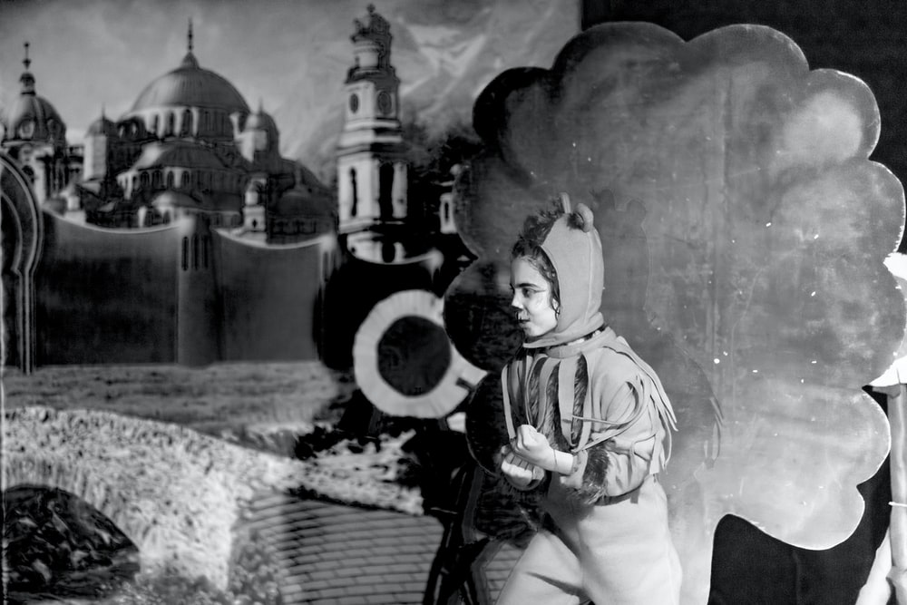grayscale photo of person wearing costume near wall
