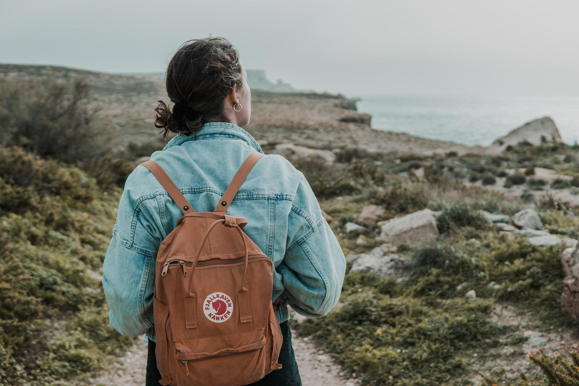 woman wearing blue denim jacket with brown backpack walking on trail near beach