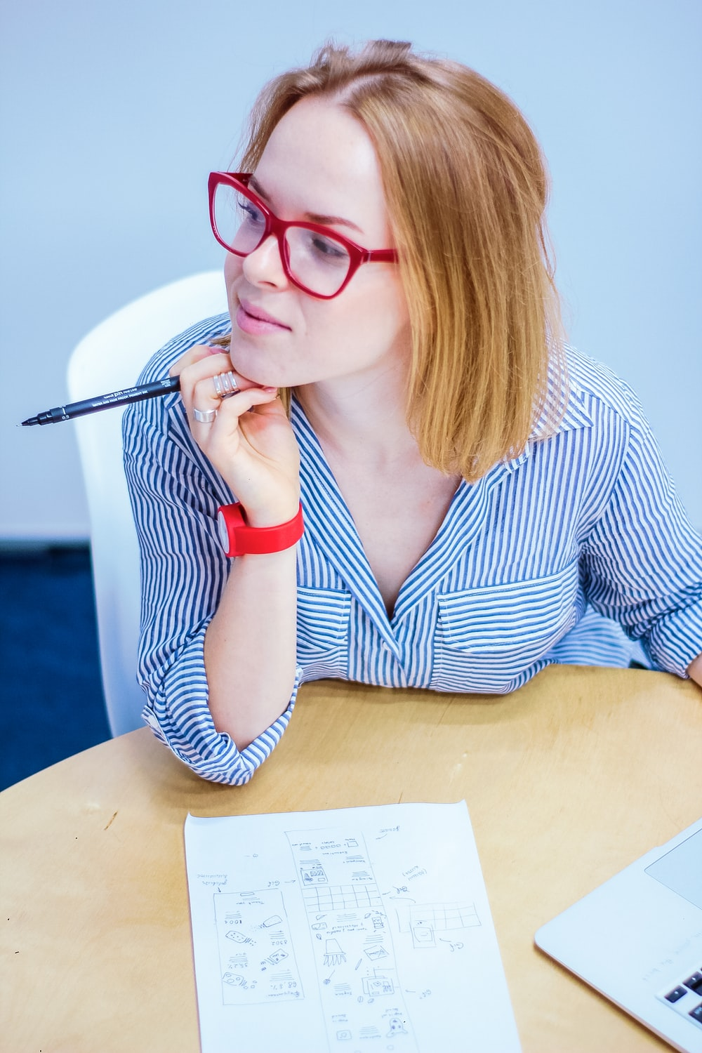 woman holding black pen sitting on white chair