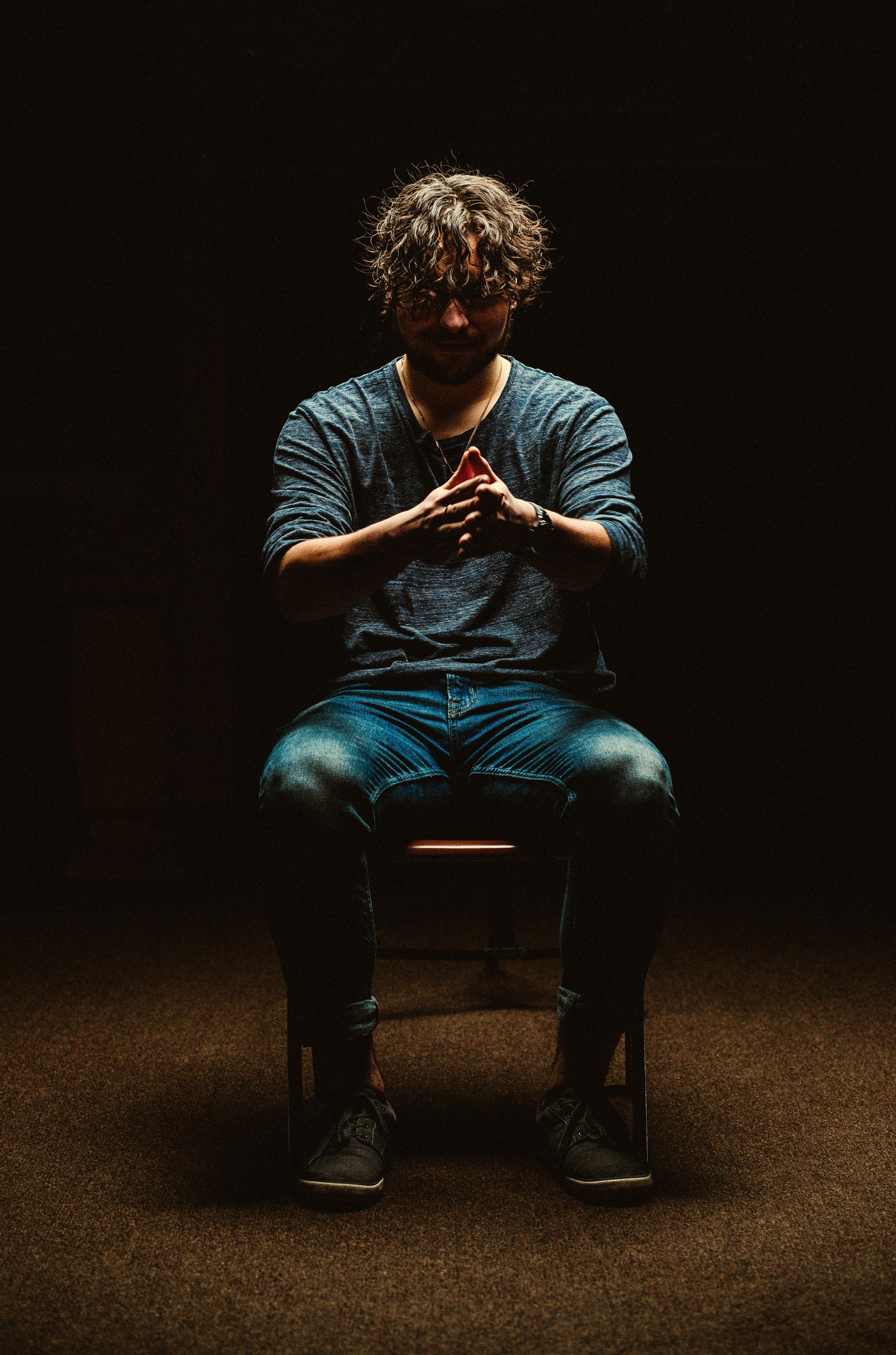 man sitting on chair inside dim room