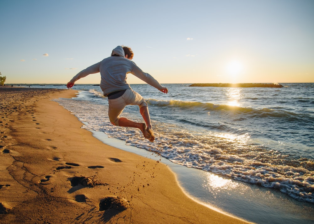 man jumping at the beach during golden hour