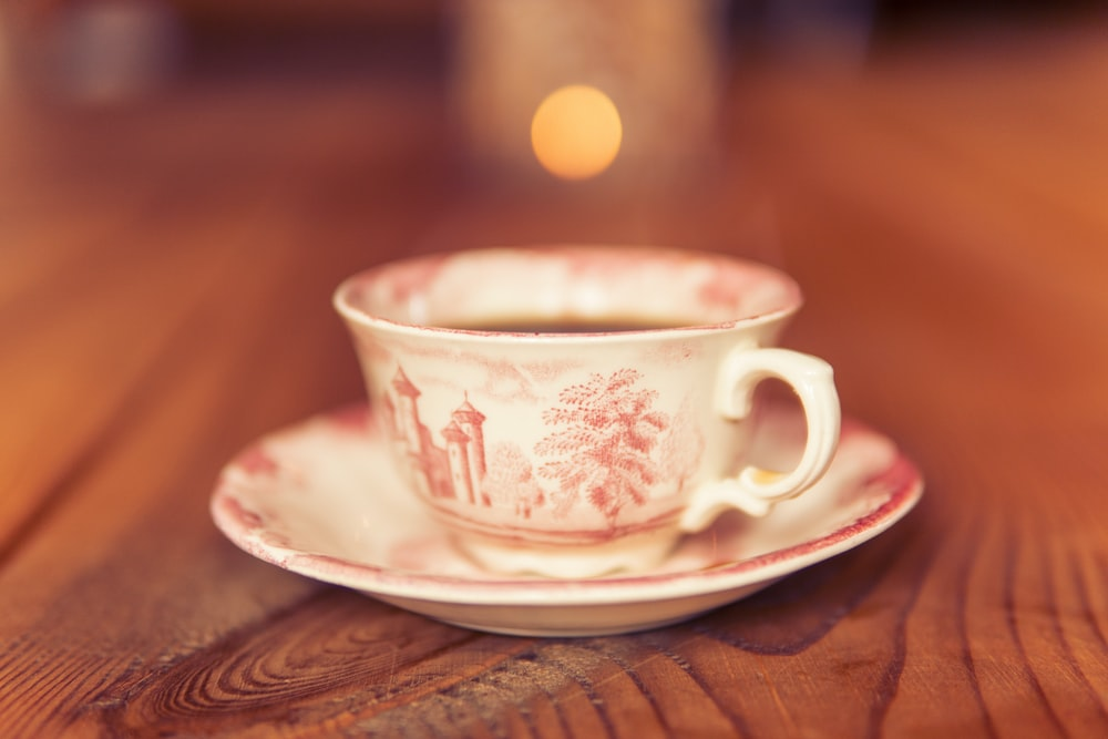 selective focus photography of white and pink teacup
