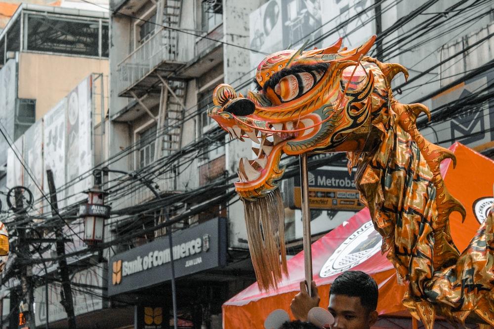 yellow dragon dance on street during daytime