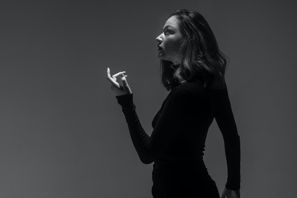 grayscale photography of woman wearing long-sleeved fitted top