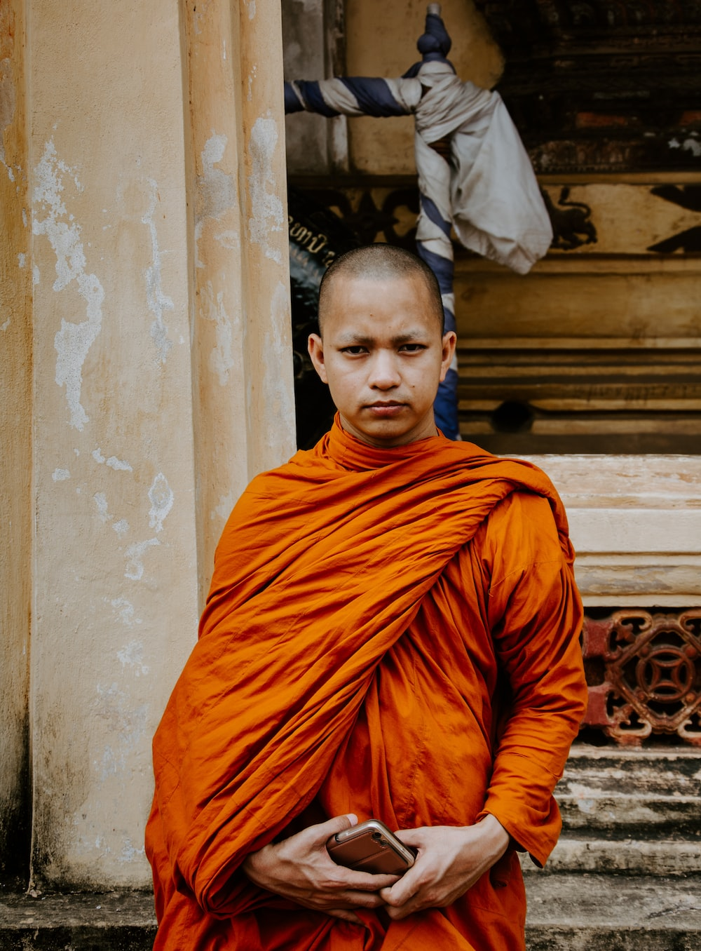 monk holding smartphone standing in front of building