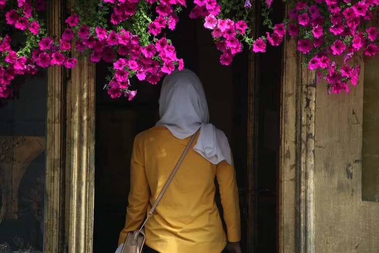 A photo of a woman wearing a headscarf, shot from behind as she walks into a darkened doorway. The building is yellow and there are bright purple flowers above the door.