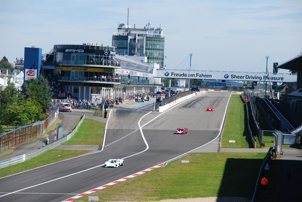 two red and white vehicles on race track during daytime