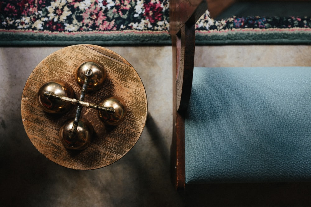 brass-colored decor beside leather padded brown wooden framed bench