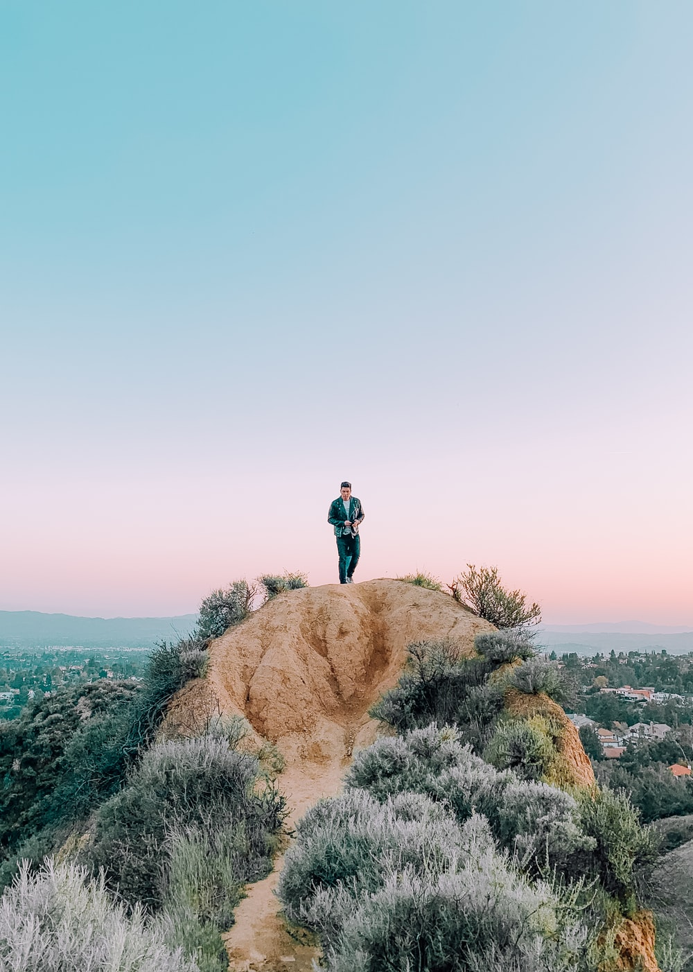 man standing on hill during daytime