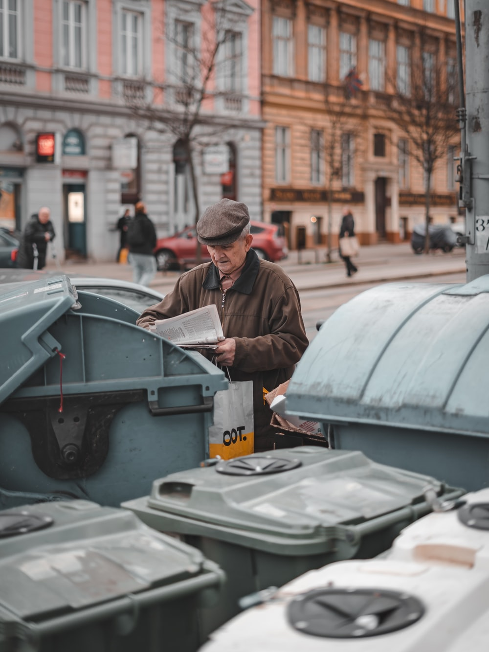 man reading paper beside trash cans