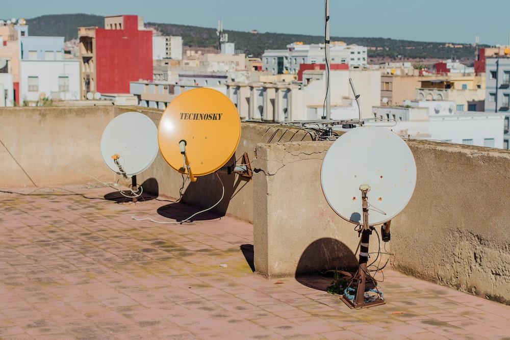 three white and yellow satellite dishes