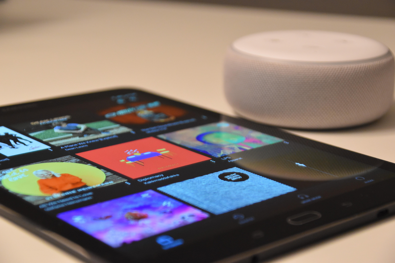 black tablet computer beside round white portable speaker
