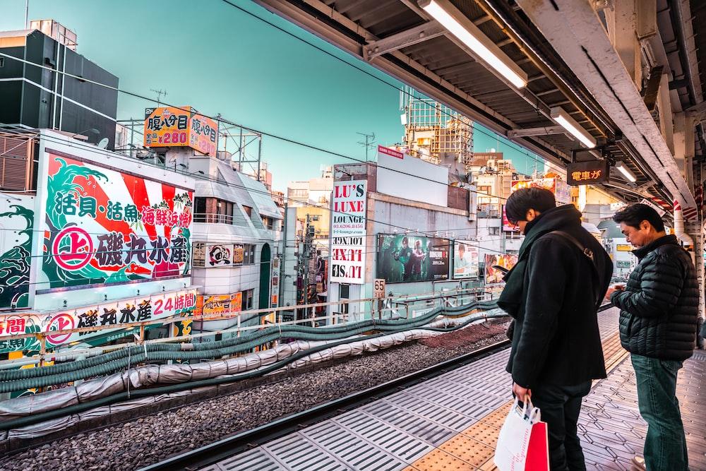 two men standing on subway during daytime