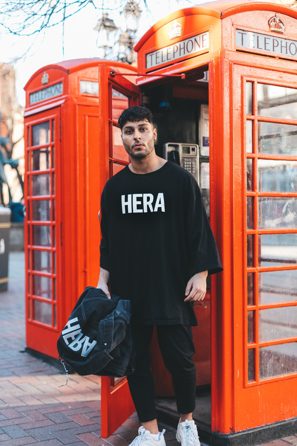man in black shirt standing near the telephone booth