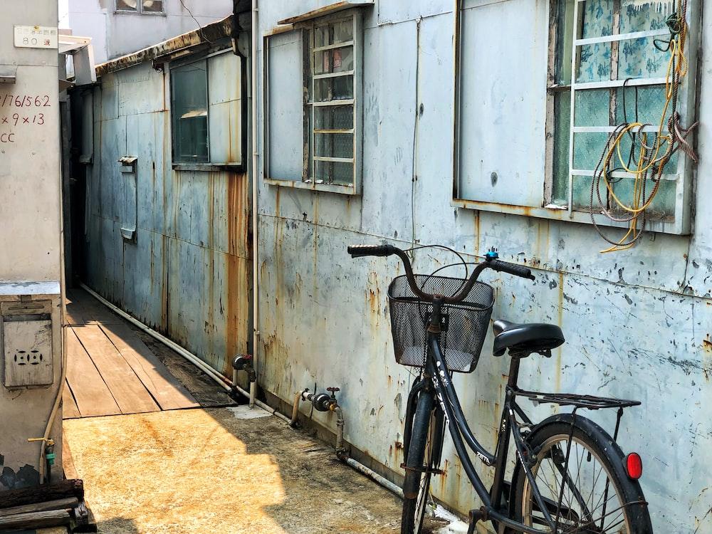 black cruiser bike parked beside white concrete house
