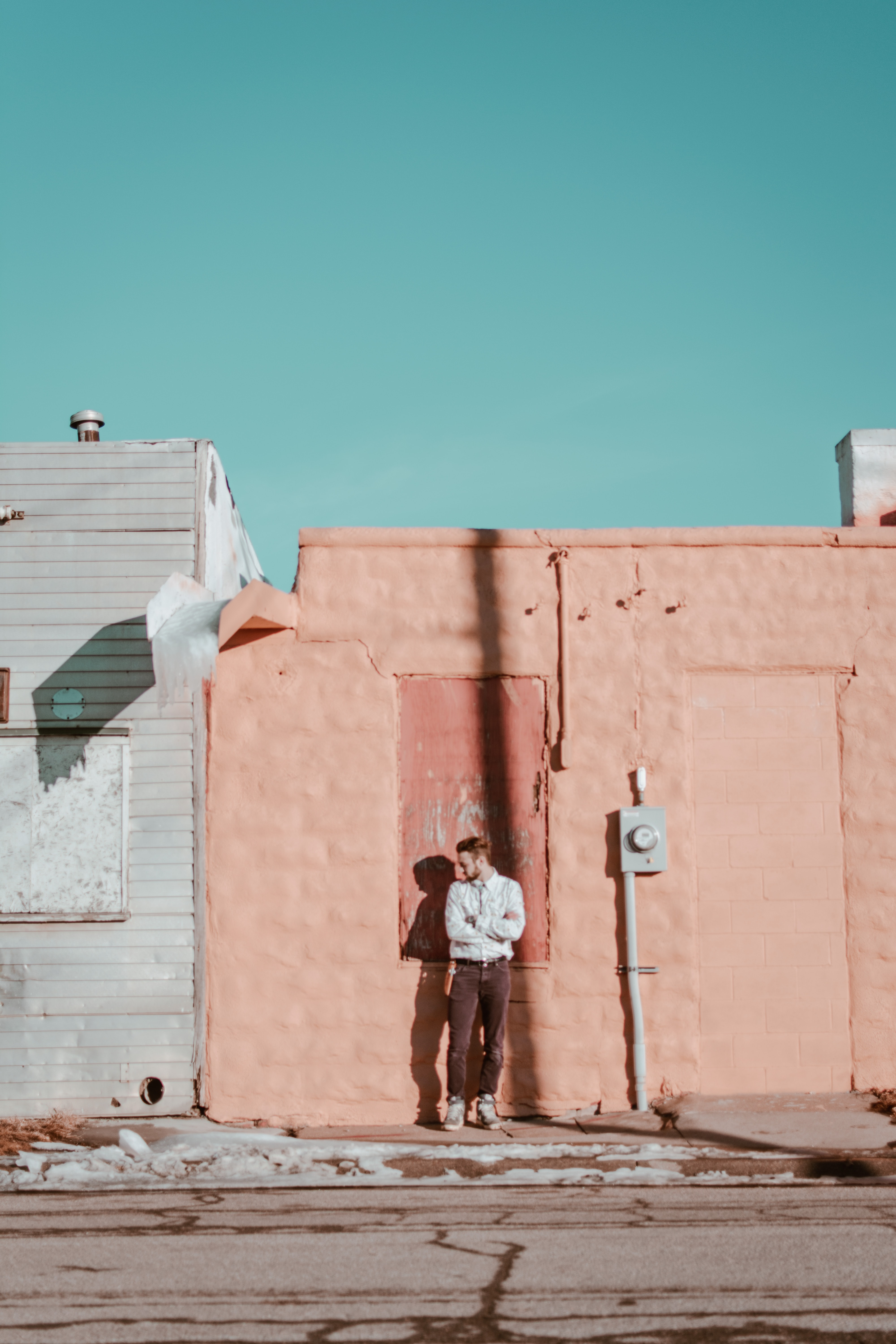 man standing in front of beige wall