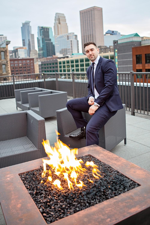 sitting man wearing blue coat beside yellow fire