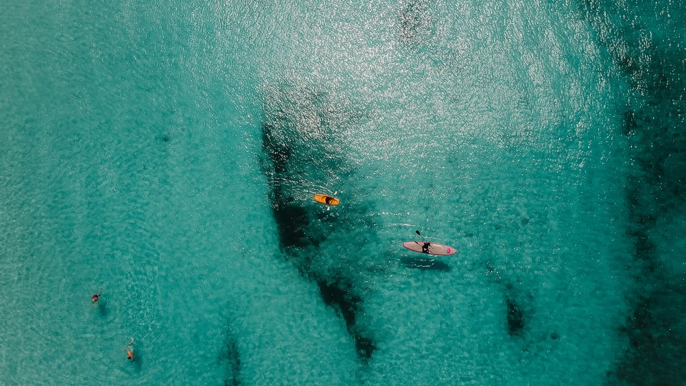 aerial view of person riding on orange kayak boats in the middle ocean