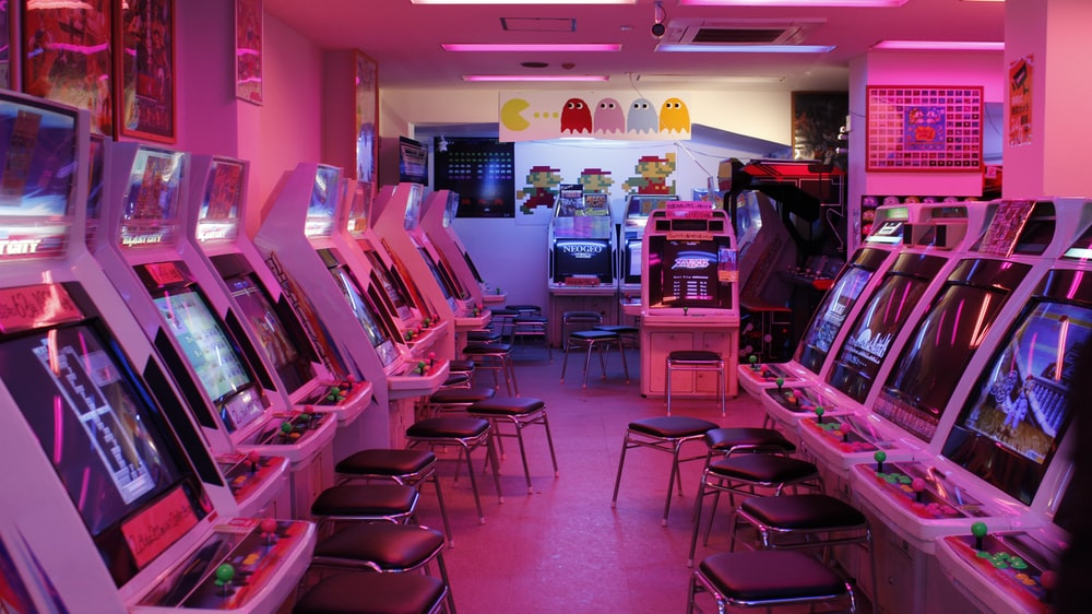 turned-on arcade machines with stools
